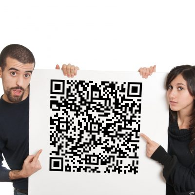 Surprised boy and girl holding a panel with qr code